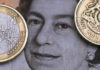 © Reuters. Photo illustration of a two Euro coin pictured next to a one Pound coin on top of a portrait of Britain