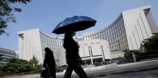 © Reuters. People walk past the headquarters of the PBOC, the central bank, in Beijing