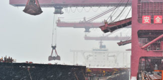 © Reuters. Cranes unload imported iron ore from a ship amid snow at the iron ore terminal of Qingdao port
