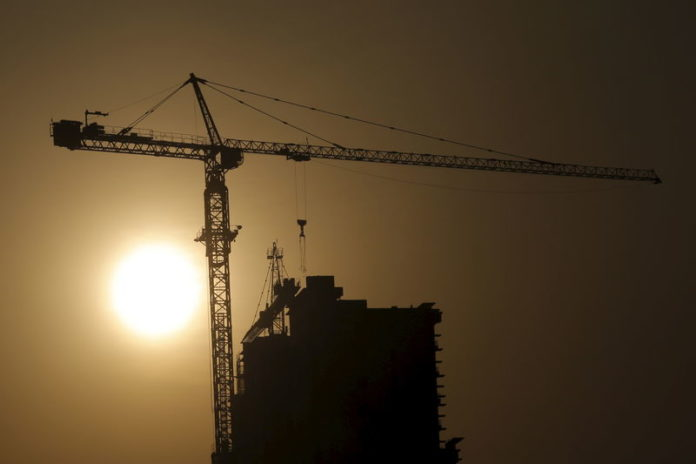 © Reuters. A crane at a construction site is silhouetted against the rising sun in Beijing