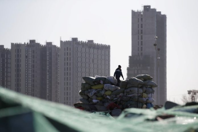 © Reuters. FILE PHOTO: A man works near apartment blocks under construction on the outskirts of Beijing, China