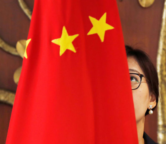 © Reuters. FILE PHOTO:  A Chinese official adjusts a Chinese flag before the start of a meeting between Foreign Minister Wang Yi and Indian Foreign Minister Sushma Swaraj in New Delhi