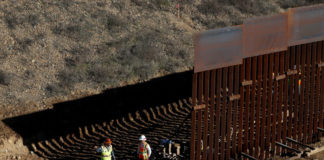 © Reuters. Workers on the U.S. side, work on the border wall between Mexico and the U.S., as seen from Tijuana