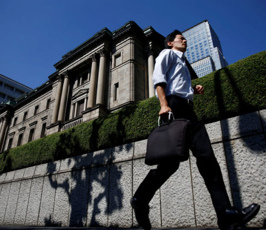 © Reuters. FILE PHOTO: A man runs past the Bank of Japan (BOJ) building in Tokyo