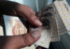 © Reuters. A man counts Egyptian pounds outside a bank in Cairo
