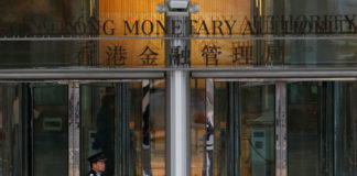 © Reuters. FILE PHOTO:  An attendant walks outside the entrance to Hong Kong Monetary Authority in Hong Kong