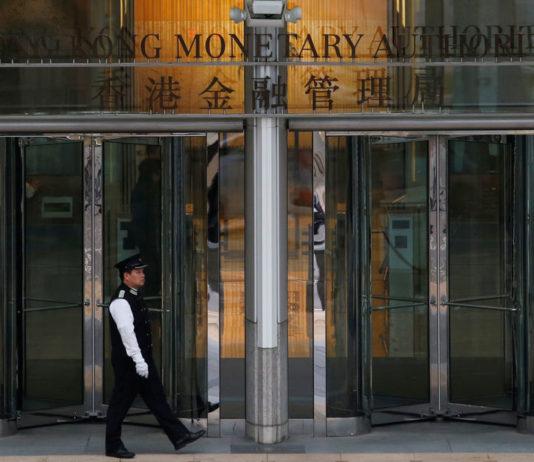 © Reuters. FILE PHOTO:  An attendant walks outside the entrance to Hong Kong Monetary Authority in Hong Kong