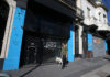 © Reuters. A man walks his dog past closed stores, in Buenos Aires