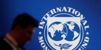 © Reuters. FILE PHOTO: A participant stands near a logo of IMF at the International Monetary Fund - World Bank Annual Meeting 2018 in Nusa Dua