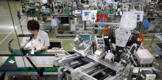 © Reuters. A humanoid robot works side by side with an employee in the assembly line at a factory of Glory Ltd., a manufacturer of automatic change dispensers, in Kazo, north of Tokyo