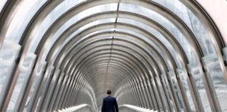 © Reuters. A businessman walks inside the Japan bridge at La Defense financial and business district in Puteaux