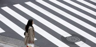© Reuters. A woman holds a shopping bag as she waits at a pedestrian crossing in the Ginza district in Tokyo