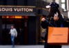 © Reuters. Woman with a Louis Vuitton-branded shopping bag looks towards the entrance of a branch store by LVMH Moet Hennessy Louis Vuitton in Vienna