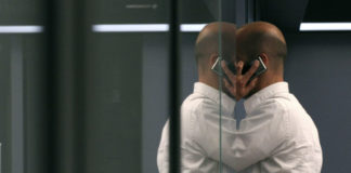 © Reuters. FILE PHOTO:  A bourse trader uses a cell phone during a trading session on the trading floor at Frankfurt