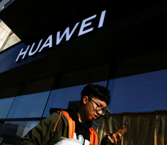 © Reuters. A man uses his phone as he walks past a Huawei shop in Beijing