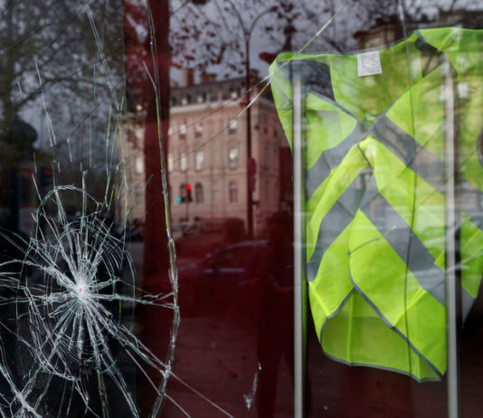 © Reuters. A yellow vest hangs inside a vandalized store front the morning after clashes with protesters wearing yellow vests, a symbol of a French drivers