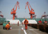© Reuters. FILE PHOTO: Workers paint the ground at a port in Qingdao