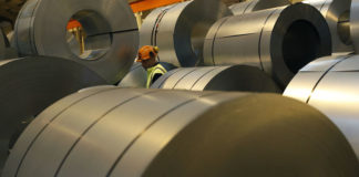 © Reuters. A worker walks through coils of steel to be used on Tata Steel