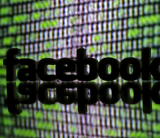 © Reuters. FILE PHOTO - 3D printed Facebook logo is seen in front of displayed cyber code
