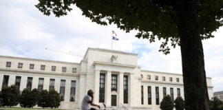 © Reuters. FILE PHOTO: A cyclist passes the Federal Reserve building in Washington