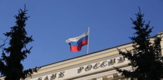 © Bloomberg. A Russian national flag flies above the headquarters of Bank Rossii, Russia