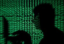 © Reuters. FILE PHOTO: Man holds laptop computer as cyber code is projected on him in this illustration picture