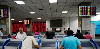 © Reuters. FILE PHOTO: Investors look at computer screens showing stock information at a brokerage house in Shanghai