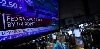 © Reuters. FILE PHOTO: A screen displays the headlines that the U.S. Federal Reserve raised interest rates as a trader works at a post on the floor of the NYSE in New York