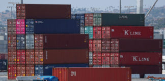 © Reuters. FILE PHOTO: Trucks offload containers from ship at the port of Los Angeles