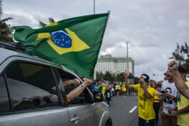 © Bloomberg. Supporters of Jair Bolsonaro, presidential candidate for the Social Liberal Party (PSL), wave a Brazilian national flag from a car while celebrating after polls closed during the second round of presidential elections in Rio de Janeiro, Brazil, on Sunday, Oct. 28, 2018. Bolsonaro swept to power in Brazil