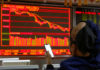 © Reuters. FILE PHOTO: An investor sits in front of displays showing stock information at a brokerage office in Beijing
