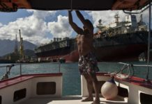 © Bloomberg. A pilot ties some knots at boat backdropped by a Petrobras oil tanker FPSO Cidade de Mangaratiba docked at Brasfels shipyard in the Jacueacanga beach, Angra dos Reis, Rio de Janeiro state , Brazil on Thursday, July 11, 2013. (Bloomberg Photo/ Dado Galdieri)