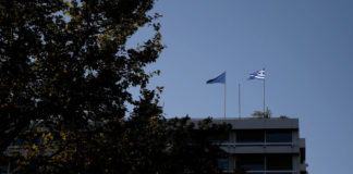 © Reuters. A Greek and a tangled EU flag flutter atop Greece