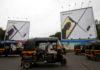 © Reuters. FILE PHOTO: Auto-rickshaws drive past the hoardings of Apple iPhone X mobile phones in Mumbai