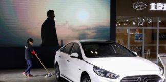 © Reuters. Worker cleans the floor next to a Sonata hybrid at a booth of Beijing Hyundai Motor in Beijing
