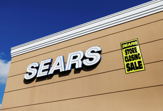© Reuters. FILE PHOTO:    A store closing sale sign is posted next to a Sears logo in New Hyde Park, New York