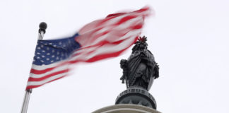 © Reuters. The U.S. flag flies near the Statue of Freedom atop the U.S. Capitol in Washington