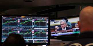 © Reuters. Federal Reserve Chairman Jerome Powell speaks on a television as traders work on the floor of the New York Stock Exchange in New York