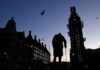 © Reuters. The sun comes up, silhouetting the statue of Churchill and Big Ben, in Westminster London