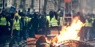 © Reuters. Protesters wearing yellow vests stand behind a barricade as they face off with police during clashes as part of a national day of protest by the