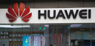 © Reuters. A woman walks by a Huawei logo at a shopping mall in Shanghai