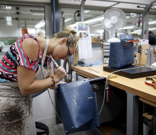 © Reuters. FILE PHOTO:  A craftswoman works on a Kelly bag at the luxury goods Hermes factory in Seloncourt
