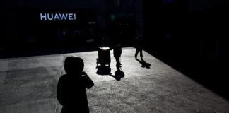 © Reuters. FILE PHOTO: People walk past a Huawei shop in Beijing