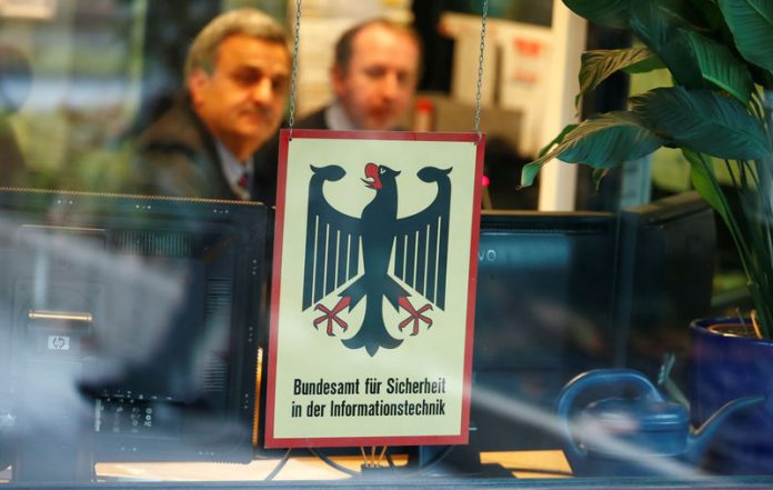 © Reuters. FILE PHOTO: Security personnel sits behind the bullet-proof window at the headquarters of Germany