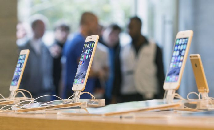 © Reuters. Customers stand in line at the Apple store in Berlin, as they wait to buy the newly released iPhone 6